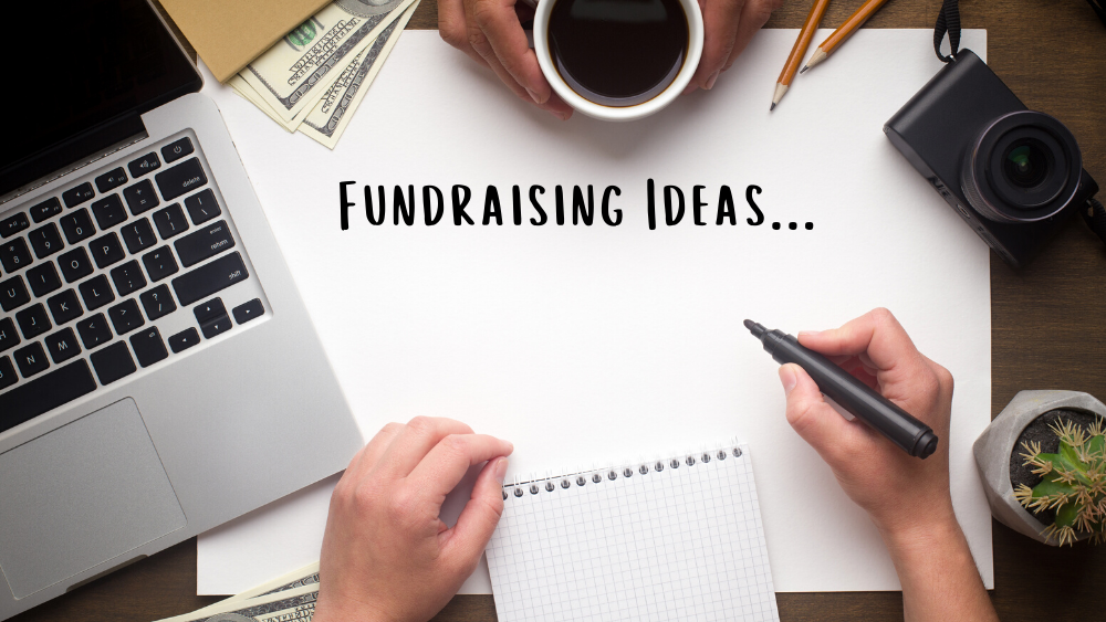 """Two people sitting across from each other with a computer, pad of paper, and a paper with the words """"Fundraising Ideas..."""""""
