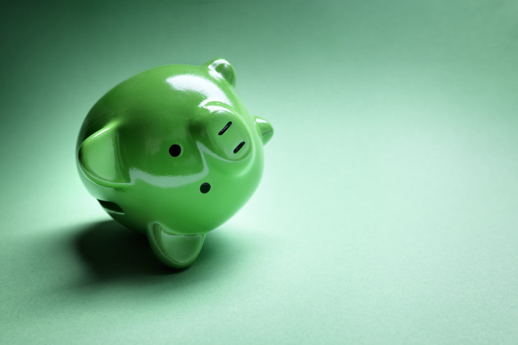 Green upside down piggy bank on a green background