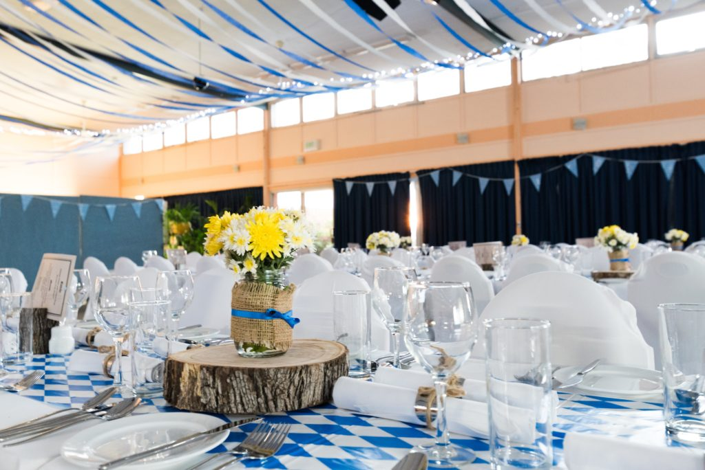 Banquet hall full of tables set for an event. Bouquet of daisies sit in a vase on top of a wooden center piece