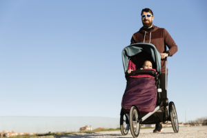Man running behind a jogging stroller with a child inside